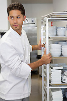 Young male chef by rack of utensils