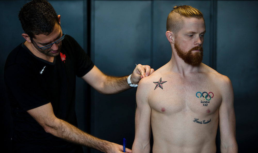 Trent Stellingwerff, applied sport physiologist with a specialization in performance nutrition performs anthropometric measurements on Geoffrey Harris at the Pacific Institute for Sport Excellence on December 3rd 2015 in Victoria, British Columbia Canada.