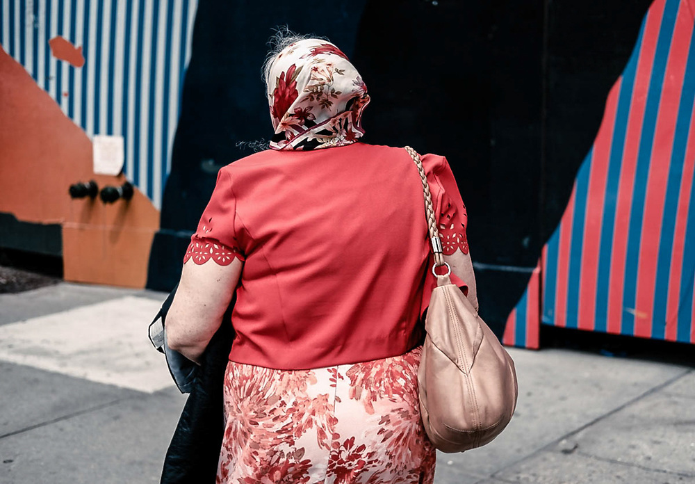Older woman in red on 34th St. striped painted building. NYC 2017<br />