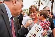 22 OCTOBER 2010 - PHOENIX, AZ:  Maricopa County Sheriff JOE ARPAIO, left, talks to SARAH PALIN and her son TRIG at a Tea Party rally in Phoenix, AZ, Friday. About 300 people attended a Tea Party rally on the lawn of the Arizona State Capitol in Phoenix Friday. They demanded lower taxes, less government spending, repeal of the health care reform bill, and strengthening of the US side of the US - Mexican border. They listened to Arizona politicians and applauded wildly when former Alaska Governor Sarah Palin and her son, Trig, made a surprise appearance. The event was a part of the Tea Party Express bus tour that is crossing the United States.     Photo by Jack Kurtz