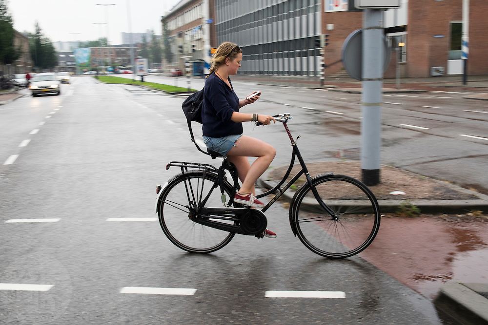 In Utrecht rijdt een meisje al kijkend op haar telefoon op de fiets door de regen terwijl een kruising over.<br /> <br /> In Utrecht cyclists a woman is crossing the street on a bicycle while she is looking at her phone.