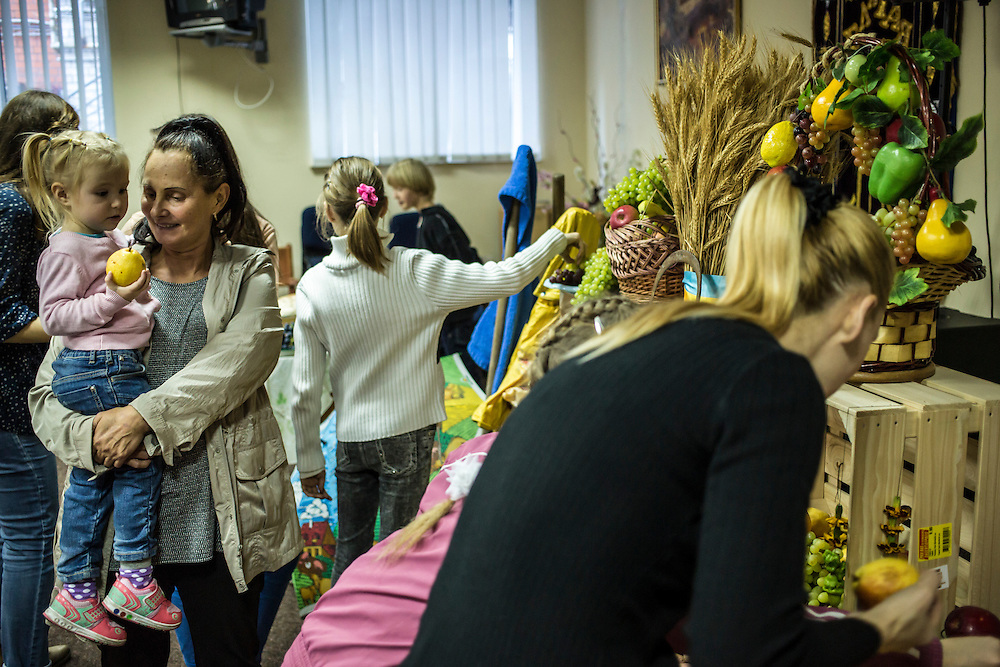 DNIPROPETROVSK, UKRAINE - OCTOBER 12: Olga Filonova (L), who fled fighting in Ukraine's East, holds her granddaughter after a service at the Good News Evangelical Church on October 12, 2014 in Dnipropetrovsk, Ukraine. Members of the congregation have opened their homes to displaced people. The United Nations has registered more than 360,000 people who have been forced to leave their homes due to fighting in the East, though the true number is believed to be much higher.(Photo by Brendan Hoffman/Getty Images) *** Local Caption *** Olga Filonova