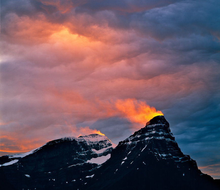 A snow plume catches light from the setting sun on Mt. Cephron in the Canadian Rockies. ©Ric Ergenbright