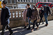 On the day that Chancellor of the Exchequer Rishi Sunak unveiled a £30bn package to boost the economy and get the country through the coronavirus outbreak, an Asian group of visitors wearing face masks walk along Whitehall in Westminster, on 11th March 2020, in London, England.