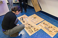 "Hempstead, New York, U.S. 12th November, 2013. Janet Hamlin, at back in black pants, a courtroom artist covering the military tribunals at Guantanamo Bay since 2006, shows her charcoal drawings and discusses her work at Hofstra University. A student is looking at sketches displayed on floor. Much of the time she was the only journalist providing a visual record of the events at the United States naval base in Cuba, and her new book ""Sketching Guantanamo"" is a collection of her images."