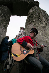 © Licensed to London News Pictures. 21/06/2015. Salisbury, UK  Picture shows Ian Norbury playing the guitar by the stones.  The Summer Solstice Festival takes place at Stonehenge.  The annual celebration of the longest day of the year, attracting tens of thousands of spectators, including Druids, tourists, locals and others.. Photo credit : Laura Dale/LNP