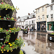 A street in Brecon, Wales, on a rainy day. At right, behind the potted plants, is the Parish Church of St Mary's.