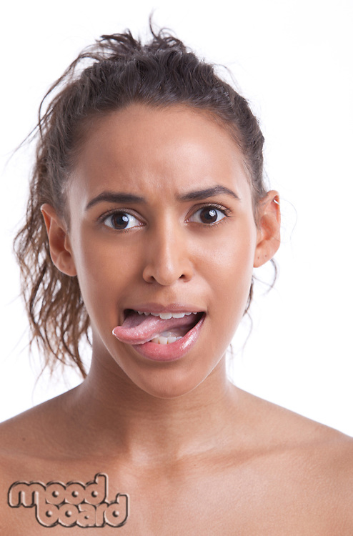 Portrait of young Mixed Race woman sticking out her tongue against white background