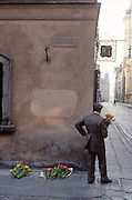 A seller of flowers stands looking down a street in the Polish capital, Warsaw. Holding a single bouquet, the elderly man has located himself on the corner of Zapiecek Street (Zapiecek means place behind the stove) awaiting a buyer. With his hand on one hip, he has laid more yellow and red flowers that he has probably grown himself and is trying to make a meagre living from. But there are few people on this street this early in the oldest part of Warsaw and the walls appear to be damp, with discoloured plaster after decades of decay under a Communist government. Old paving slabs on the pavement and a cobbled road give a sense of history and wartime destruction for these streets saw many atrocities during the German occupation in WW2. This is a scene of pessimism and poverty yet with a small degree of hope in the fresh flowers.