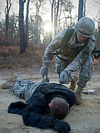 April 9, 2011, Camp Edwards, MA - Cadet Jon Broderick searches a forth year cadet who was portraying a member of an opposition force. Cadets are taught to practice proper search techniques during their field training exercises. Photo by Lathan Goumas.