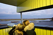 "Visitors viewing the Oostverdesplassen nature reserve. The reserve is a wilderness that was constructed from reclaimed land. The reserve occupies fourteen thousand perfectly flat acres on the shore or the inlet turned lake. This area was originally designated for industry; however while it was still in the process of drying out, a handful of bioligist convinced the Dutch government that theland would be better used to recreate a paleolithic landscape. The biologist set aboutstocking the Oostverdesplassen with the sorts of animals that would have inhabited the region since prehistoric times had it not been underwater. For example, Heck cattle, were used in place by the extinct aurochs, these are cattle of a variety specially bred by Nazi scientists. The cattle grazed and multiplied, so did the red deer, the wild horses, the egrets, the geese and foxes. All were brought in from other countries. These mammals reproduced so prolifically that the German magazine Der Spiegel dubbed the Oostvaardesplassen ""the Serengeti behind the dikes."" Flevoland, Netherlands."