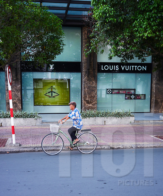 An old vietnamese man rides his bicycle on Dong Khoi Street, Ho Chi Minh City, Vietnam, Southeast Asia