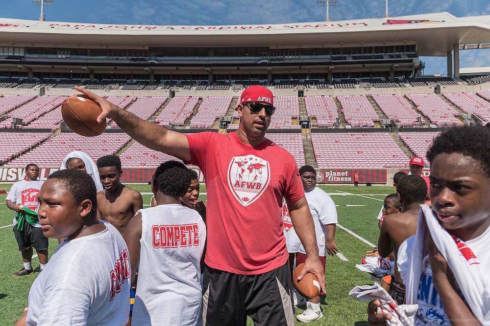 Breno Giacomini, a co-founder of the American Football Without Barriers youth football camp, gives students directions to new drills at the University of Louisville's Papa John's Cardinal Stadium. June 25, 2016