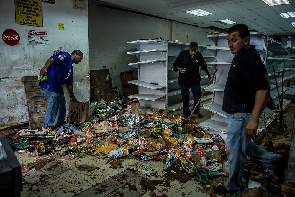 CARACAS, VENEZUELA - APRIL 21, 2017:  Staff work to clean the Ofercenter supermarket that was one of over a dozen stores looted late last night in El Valle, a working class neighborhood in Caracas. The streets of Caracas erupted into a night of riots, looting and clashes with National Guardsmen as anger from two days of pro-democracy protests spilled into unrest in working class neighborhoods and slums. Shots rang out throughout the night in El Valle, a neighborhood of mixed loyalties, as armored vehicles struggled to contain crowds of looters. At one point during the night, clashes became so heavy that a nearby children's hospital was evacuated after the ward filled with tear gas. The government said they were responding to an attack on the hospital by opposition protestors.  PHOTO: Meridith Kohut