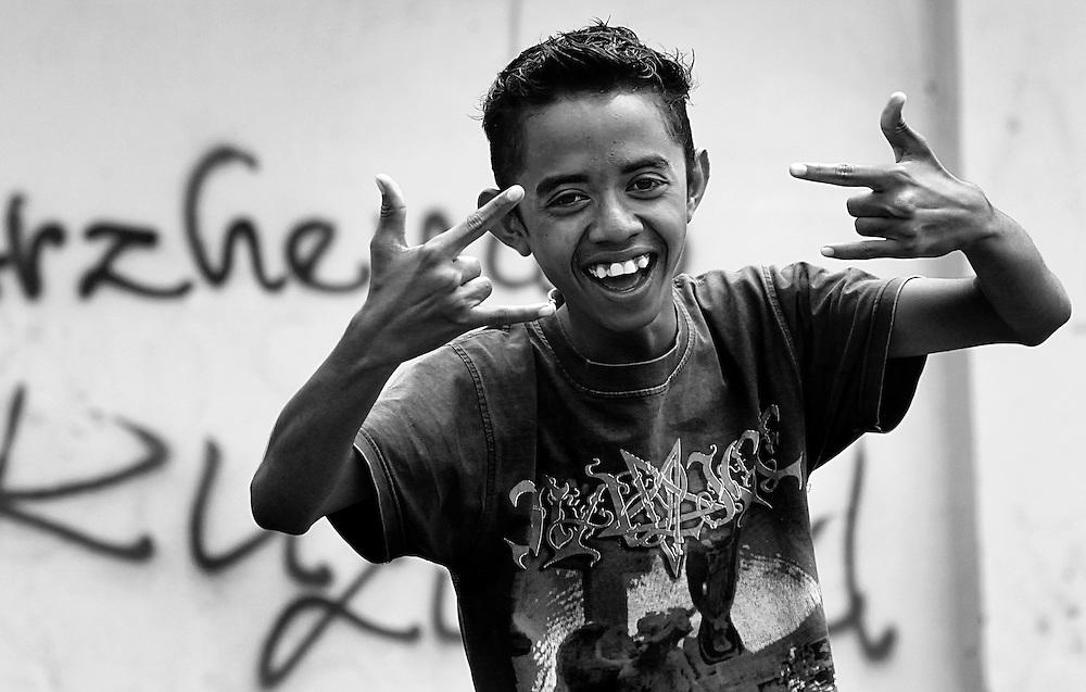 A boy outside a wall bearing graffiti on Flores Island, Indonesia.