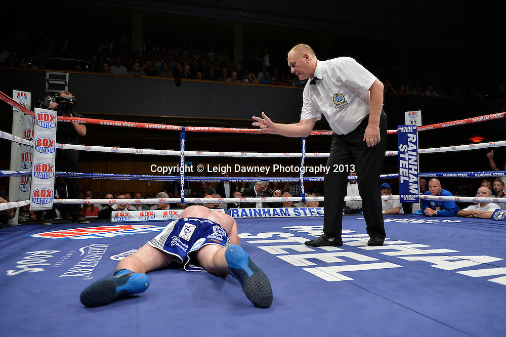 Leonard Bundu throws a body shot on Frankie Gavin. The referee counts Gavin before he returns to his feet during the European & Commonwealth Welterweight Championship at Wolverhampton Civic Hall, Wolverhampton, 1st August 2014. Promoted by Frank Warren in association with PJ Promotions. © Credit: Leigh Dawney Photography.