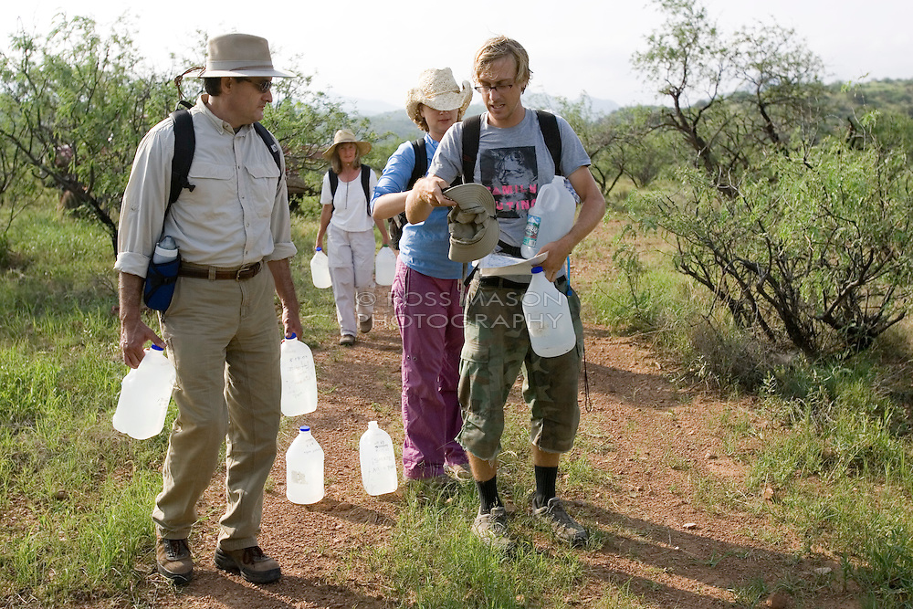"Camp director Andrew ""Budge"" Burridge (right) prepares to take the group out on the morning patrol of the desert trails surrounding the No More Deaths camp in Southern Arizona. Each volunteer carries 2 4-litre jugs of water that is left along the trails for migrants passing through the area. The jugs are dated so the group has an idea of when people have travelled along a certain trail."