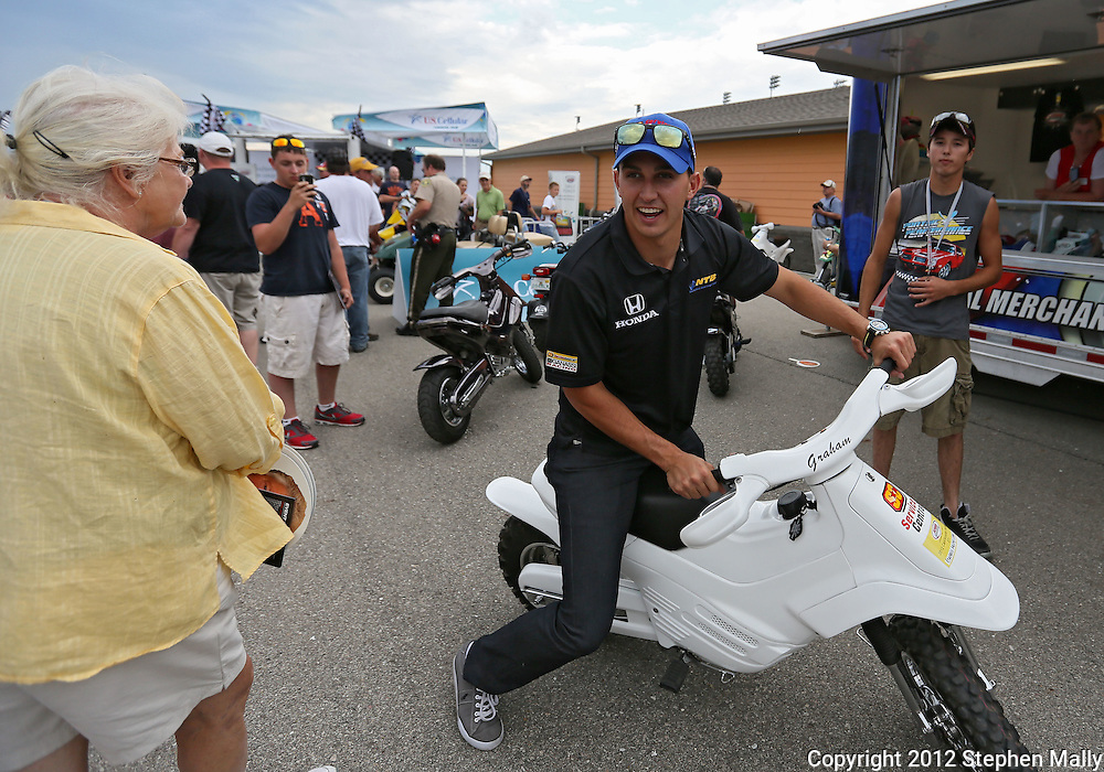 Graham Rahal leaves an autograph session on a motorbike before the start of the IZOD IndyCar Iowa Corn Indy 250 auto race at the Iowa Speedway in Newton, Iowa on Saturday, June 23, 2012.