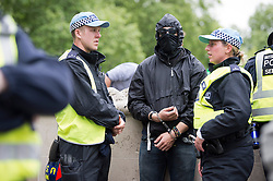 © London News Pictures. 11/06/2013. London, UK.  An Anti-G8 activist being detained in handcuffs by police  ahead of an anti G8 demonstration in central London today (Tues). The G8 Summit is due to take place in Norther Ireland early next week.  Photo credit: Ben Cawthra/LNP
