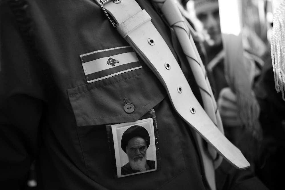 One flag-bearer also wears a portrait of Ayatollah Ruhollah Khomeini, Iran's supreme leader from 1979 to 1989.