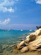 windwept rocks and boats in the Cala Gilgolu<br /> Costa Smeralda  Sardinia  Italy