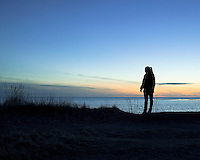 A woman looking out towards the sea late at night