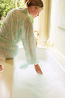 Woman in bathrobe bending down over bathtub filled with bubbles testing water back view