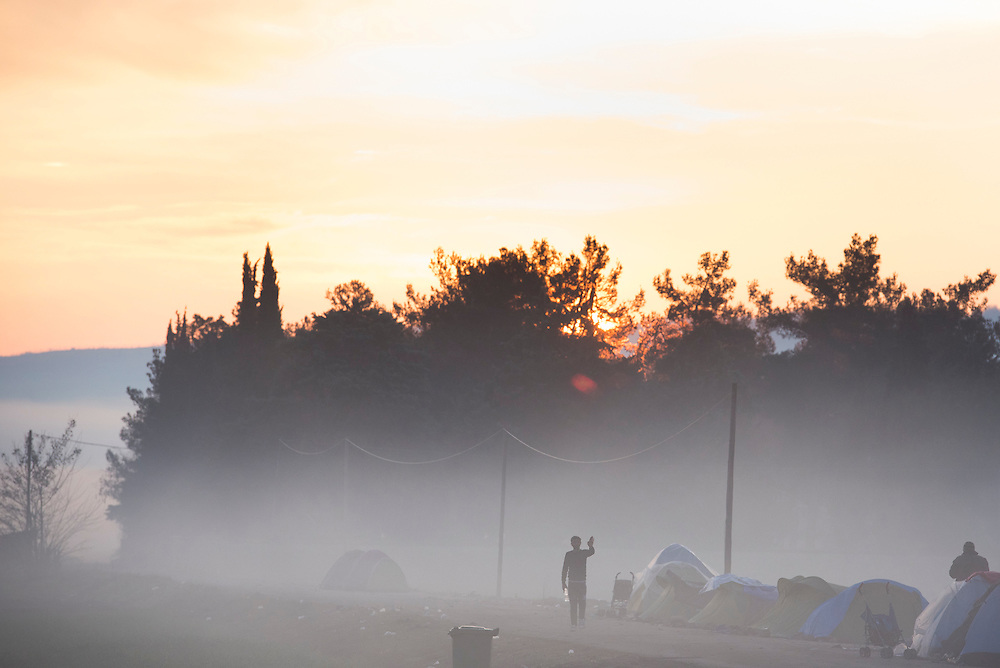 A refugee walks along a road at sunrise at a camp on the Macedonian (FYROM) border on March 11, 2016 in Idomeni, Greece.