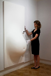 © Licensed to London News Pictures. 08/10/2012. LONDON, UK. A member of Bonhams staff examines 'Belly Door' (2007) (est. GB£10,000-15,000) by Scandinavian artists Elmgreen and Dragset ahead of a sale at the auction house's New Bond Street premises. The auction, featuring a collection of contemporary art and design is set to take place on Thursday the 11th of October at Bonham's New Bond Street auction house. Photo credit: Matt Cetti-Roberts/LNP