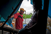 A grandfather takes a moment rest under his makeshift tarp roof. His daughter in the foreground is pregnant with her second child. Image © Jonah Markowitz/Falcon Photo Agency