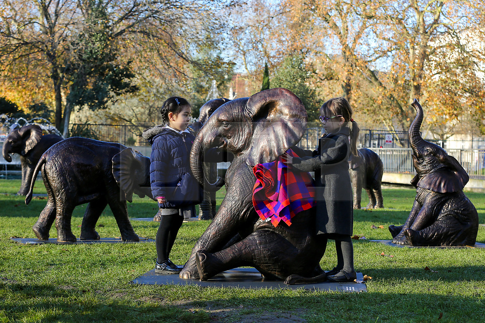 © Licensed to London News Pictures. 04/12/2019. London, UK. 4 years old Georgiana Chubb (R) and 5 years old Rosalind Cheung (L) from Hampden Gurney Primary School put a blanket on a sculpture of an elephant in at Marble Arch during an unveiling of life-sized herd of 21 bronze elephants.<br /> The sculpture is the largest such depictionof an elephant herd in the world and is intended to draw attention to the plight of this species that could be extinct on current trends, by 2040. Each elephant in the sculpture is modelled after a real orphaned animal currently in the care of the Sheldrick Wildlife Trust. Left behind by poachers and other sources of human-wildlife conflict these animals have been raised by the trust in an effort to secure the future of the species. The herd will be displayed until 4 December 2020. Photo credit: Dinendra Haria/LNP