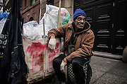 "17 November 2013 - New York, NY [Austin ""Guy"" Butler waits outside a Manhattan apartment building for the maintenance man to bring out the recycling.  Much of Butler's time is spent waiting in order to guarantee that no one else takes anything of value.] 11/17/13 Stoneham/CUNY Journalism Photo"