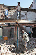 Men work on constructing another structure in the midst of the slum.  The slum of Cheetah Camp on the outskirts of Mumbai, India is a predominantly muslim community on living on the fringe while the city continues to grow.