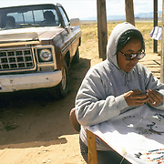 December morning on the Navajo Reservation a Navajo woman is beading necklace for the tourist at road side stand on their way to Monument Valley UT. Her husband children are in pickup truck behind.