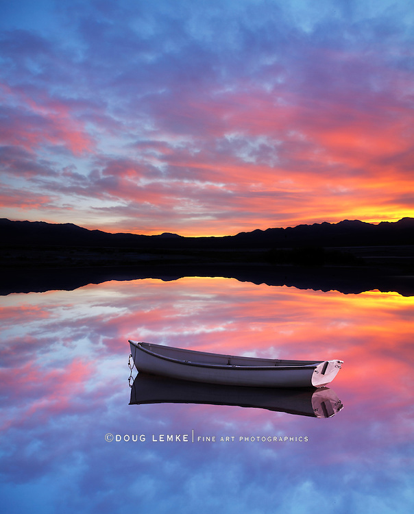 A Very Colorful Mythical Sunset Over Mountains, Water And A Small Row Boat At Anchor. This Is A Digital Composite Image