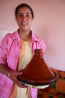 Berber teenager in a village in the high Atlas Mountains, near Marrakech, Morocco, carrying a tagine