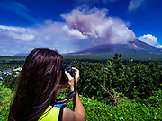 "22 JANUARY 2018 - CAMALIG, ALBAY, PHILIPPINES: A woman takes pictures of an eruption of the Mayon volcano. There were a series of eruptions on the Mayon volcano near Legazpi Monday. The eruptions started Sunday night and continued through the day. At about midday the volcano sent a plume of ash and smoke towering over Camalig, the largest municipality near the volcano. The Philippine Institute of Volcanology and Seismology (PHIVOLCS) extended the six kilometer danger zone to eight kilometers and raised the alert level from three to four. This is the first time the alert level has been at four since 2009. A level four alert means a ""Hazardous Eruption is Imminent"" and there is ""intense unrest"" in the volcano. The Mayon volcano is the most active volcano in the Philippines. Sunday and Monday's eruptions caused ash falls in several communities but there were no known injuries.    PHOTO BY JACK KURTZ"