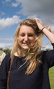 Model released blonde haired young woman smiling outside on a windy day with her hair blowing across her face, UK