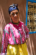 Berber lady stands infront of her home in the High Atlas Mountains, Morocco