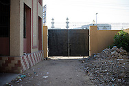 The backside of the gate of the Women's police station, closed off most of the time. <br /> Women's police stations were founded from 1994 onwards by then Prime Minister Benazir Bhutto. <br /> Initially set up to investigate cases of violence against women and have them handled by female police officers, the reality on the ground is often very different. With limited authority and hardly any female police officers on duty, they don't fully serve the purpose they were intended for. Karachi, Pakistan, 2011