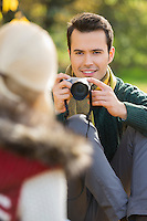 Smiling young man photographing woman in park