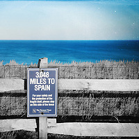 Sign on Nantucket Island, Massachusetts, giving the distance to Spain. 50s studio style with added textures.