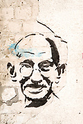Graffiti of Mahatma Gandhi on an old dilapidated cracked wall. Photographed in Israel