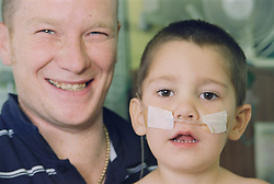 Portrait of father and son with oxygen tube across his face on children's renal ward,