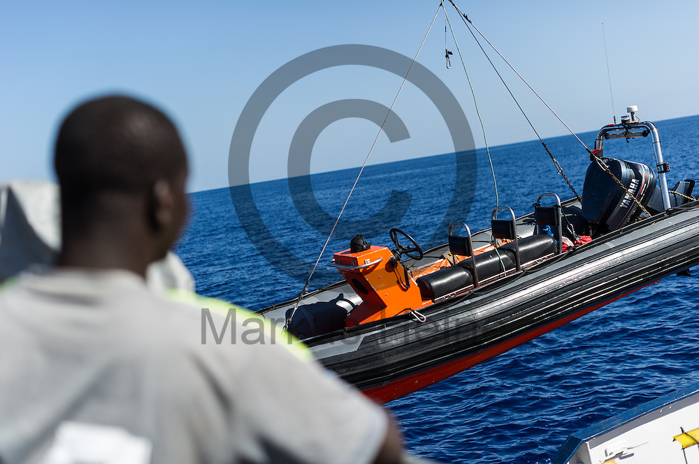 Ein Fluechtling schaut am 22.09.2016 auf dem Fluechtlingsrettungsboot Sea-Watch 2 in internationalen Gewaessern vor der libyschen Kueste zu wie ein RIB (Schlauchboot) aus dem Wasser geholt wird. Foto: Markus Heine / heineimaging<br /> <br /> ------------------------------<br /> <br /> Veroeffentlichung nur mit Fotografennennung, sowie gegen Honorar und Belegexemplar.<br /> <br /> Publication only with photographers nomination and against payment and specimen copy.<br /> <br /> Bankverbindung:<br /> IBAN: DE65660908000004437497<br /> BIC CODE: GENODE61BBB<br /> Badische Beamten Bank Karlsruhe<br /> <br /> USt-IdNr: DE291853306<br /> <br /> Please note:<br /> All rights reserved! Don't publish without copyright!<br /> <br /> Stand: 09.2016<br /> <br /> ------------------------------