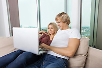 Young couple using laptop in living room at home