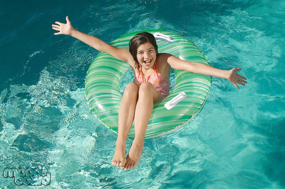 Girl in inflatable raft in swimming pool, portrait
