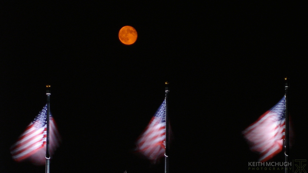 Patriotism at its finest.  Three American flags flanked by a harvest moon at the Washington Monument