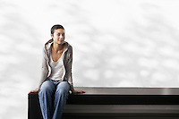 Young woman sitting indoors on bench portrait