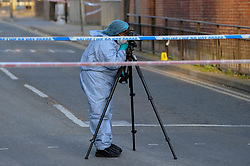 © Licensed to London News Pictures. 06/05/2018. LONDON, UK. A member of the forensics team at work as police cordon off Palmerston Road in Wealdstone, near Harrow, north west London, following reports of two separate shooting incident around midday on Sunday 6 May 2018.  The two victims are a 12 year old boy and a15 year old boy.  Investigations are ongoing.  Photo credit: Stephen Chung/LNP